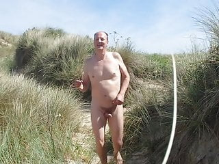 Male nudist dancing naked & free in the beach dunes.